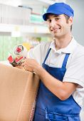 stock photo of scotch  - Young attractive sales clerk at work holding scotch tape and cardboard box - JPG