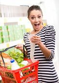 picture of receipt  - Astonished young woman with full shopping basket checking a grocery receipt - JPG