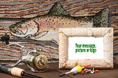 stock photo of musky  - Reel pole bobbers jig on table with fish in background - JPG