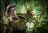 picture of rainforest  - Young explorer guy walking in the rainforest jungle with exploration equipment and thick glasses.