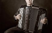 picture of accordion  - Musician playing the accordion against a black background - JPG