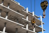 picture of crane hook  - Crane hooks and new concrete building is under construction - JPG