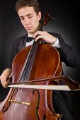 stock photo of cello  - Cellist playing classical music on cello on black background - JPG