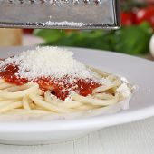 stock photo of grating  - Cooking spaghetti noodles pasta food grating Parmesan cheese on plate - JPG