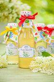 foto of elderflower  - Bottles with elderflower syrup in the garden - JPG