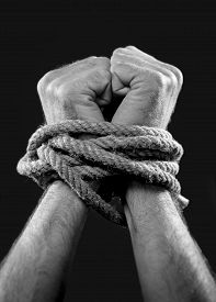 stock photo of human-rights  - white man hands wrapped with rope around wrists in captivity victim abused slave of work respect for human rights and exploitation concept isolated on black background - JPG