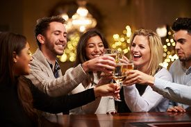pic of alcoholic drinks  - Group Of Friends Enjoying Evening Drinks In Bar - JPG