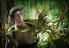 pic of rainforest  - Young explorer guy walking in the rainforest jungle with exploration equipment and thick glasses. ** Note: Soft Focus at 100%, best at smaller sizes - JPG