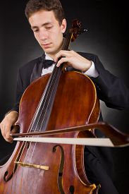 image of cello  - Cellist playing classical music on cello on black background - JPG