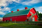 pic of red roof  - A long barn painted bright red with green roof under a bright blue sky in the country - JPG