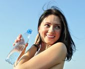 picture of hot-weather  - cheerful young woman holding bottle of cold water in hot weather - JPG
