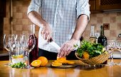 picture of sangria  - Man cuts oranges for making sangria for home party - JPG