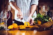 image of sangria  - Man cuts oranges for making sangria for home party - JPG
