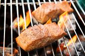stock photo of grill  - Grilled salmon on the flaming on fire in the grill.