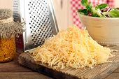 foto of grating  - Grated cheese on wooden cutting board in kitchen - JPG