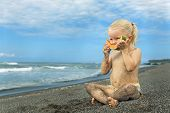 pic of tropical food  - After playing on the sea black sand beach little cute girl picnics of natural vegetarian food  - JPG