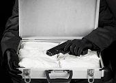 stock photo of drug dealer  - Criminal holding gun over briefcase full of drugs - JPG
