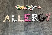 pic of allergy  - The word allergy written with pills on a wooden background - JPG