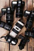 stock photo of megapixel  - Modern cameras on wooden table - JPG