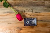 foto of heart sounds  - rose and vintage audio cassette with loose tape shaping one heart on a wooden background - JPG