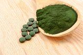 stock photo of algae  - Closeup of an organic spirulina algae powder and pills in a wooden spoon - JPG