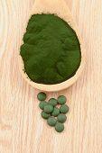 picture of algae  - Closeup of an organic spirulina algae powder and pills in a wooden spoon - JPG