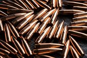 picture of gun shot  - Placer copper bullets on a dark wooden background - JPG