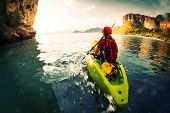 foto of kayak  - Young lady paddling the kayak in a calm bay with limestone mountains - JPG