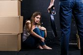 picture of abused  - Young woman is a victim of domestic violence and abuse siting on the floor is scared of man with belt - JPG