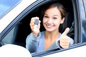foto of car-window  - Happy girl in a car showing a key and thumb up gesture  - JPG