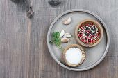 image of ceramic bowl  - Two wooden bowls with salt and multicolored pepper and thyme sprigs in a ceramic plate on a wooden board with space for text - JPG