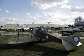stock photo of biplane  - Old biplane in front of modern fighters at aircraft base - JPG