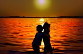 foto of pretty-boy  - Silhouette of boy and dog embracing at sunset - JPG