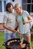 foto of tong  - Women helping boyfriend husband at outdoor garden barbecue with tongs and beer - JPG