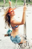 foto of swing  - Beautiful Cheerful Woman Swinging by the Beach - JPG