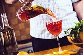 picture of sangria  - Man pours homemade sangria with fruit pieces in a glass. Refreshing summer drinks