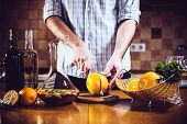 foto of sangria  - Man cuts fresh grapefruits for making sangria for home party - JPG
