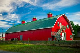 stock photo of barn house  - A long barn painted bright red with green roof under a bright blue sky in the country - JPG