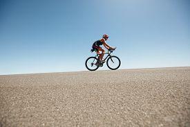 picture of triathlon  - Female cyclist on a country road training for triathlon - JPG