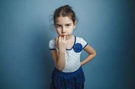 stock photo of finger-licking  - a girl of seven European appearance brunette stuck a finger in his mouth on a gray background - JPG
