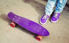 picture of snickers  - Teenager feet in jeans and snickers with skateboard photo with retro tonal correction instagram old style - JPG