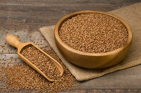 pic of buckwheat  - Buckwheat groats in a bowl and wooden scoop with buckwheat on grunge background - JPG