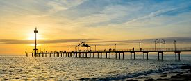 stock photo of jetties  - People fishing and walking on the Brighton jetty at sunset - JPG