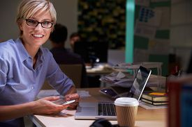 foto of late 20s  - Female Office Worker With Coffee At Desk Working Late - JPG