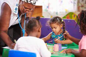 foto of teachers  - Teacher helping kids in a preschool class - JPG