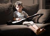 Постер, плакат: Мальчик играет электронная гитара игры несколько зернистые изображения
