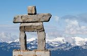 giant rock inukshuk with mountains - inuit symbol for 'the way'