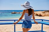 Portrait Of Beautiful Tanned Woman At The Sea Coast In Hat And Retro Style Clothes. Hot Summer Day A poster