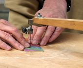 picture of peddlers  - Peddler using foot powered jigsaw machine to cut names - JPG