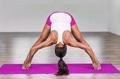 Yoga girl doing wide leg forward fold at gym. Woman stretching legs muscles doing Prasarita Padottan poster